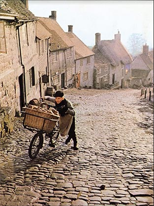 A still from the iconic Hovis advert of the bakery delivery boy pushing his bike up a steep hill.