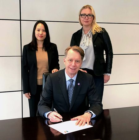 Photograph of Peter Lukasiewicz, CEO of Gowling WLG Canada, signs the Accord alongside energy partner Irene Choe and energy associate Magda Hanebach.
